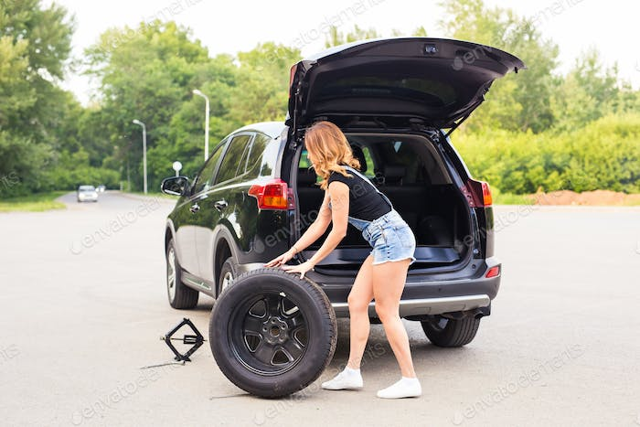 Woman changing tire on a road
