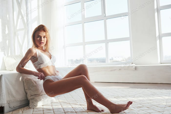 Full body picture. Portrait of a sexy redhead girl on the floor posing in the white room