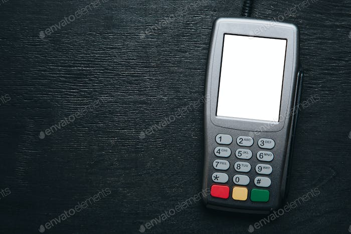Credit card terminal on dark wooden desk