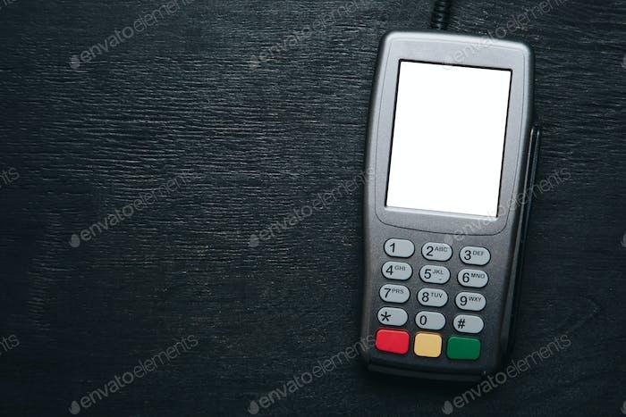 Credit card terminal on dark wooden desk