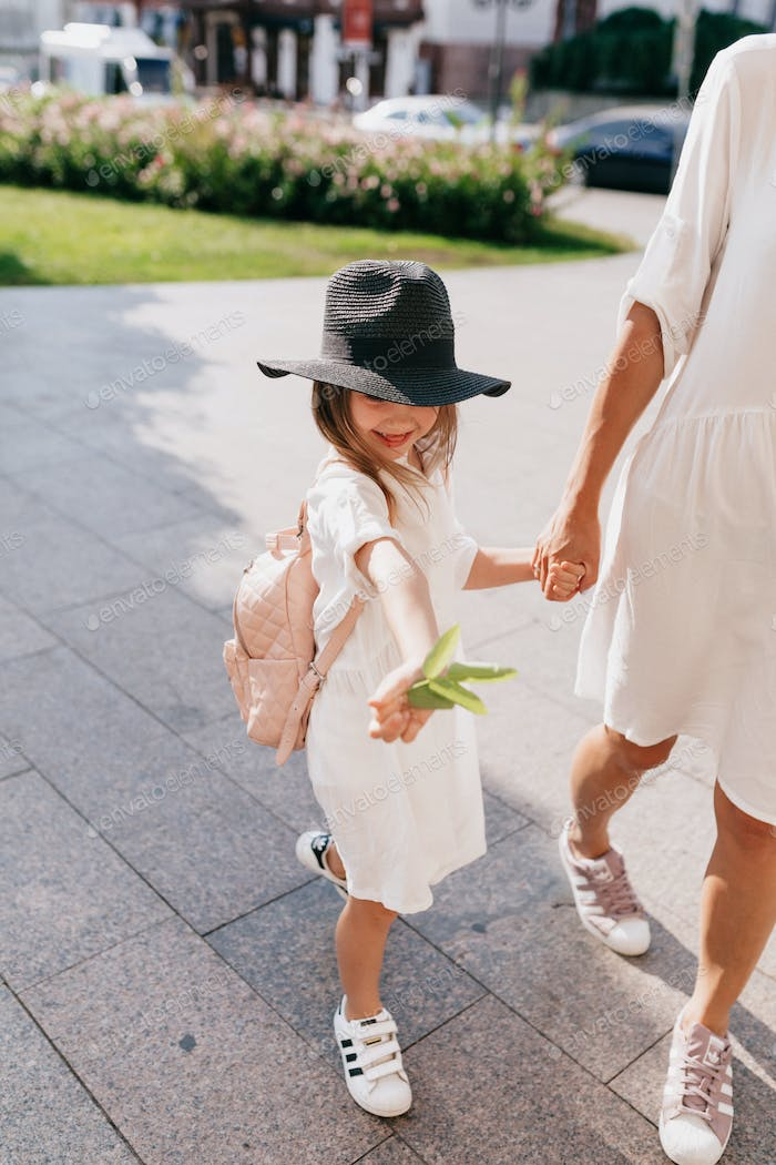 Stylish kid in summer dress and hat walking down with mother while traveling