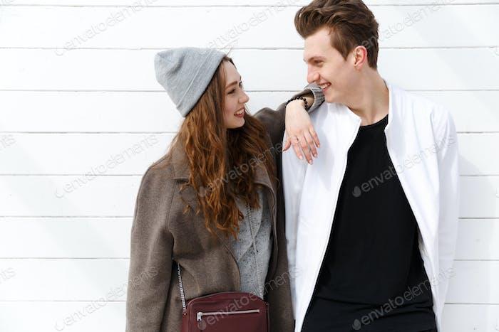 Fröhliches junges Paar stehen und schauen einander an