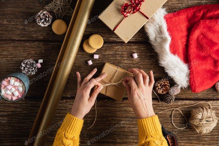 Hände wickeln Weihnachtsgeschenke