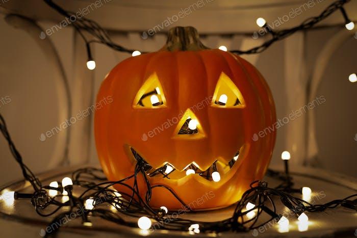 Jack o Lantern pumpkin with light garland on dark