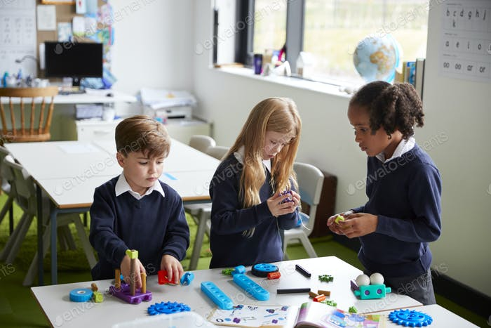 Elevated view of three primary school kids working together using construction blocks in a classroom