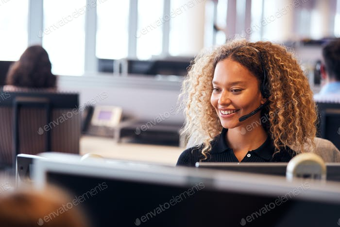 Young Businesswoman Wearing Telephone Headset Talking To Caller In Customer Services Department