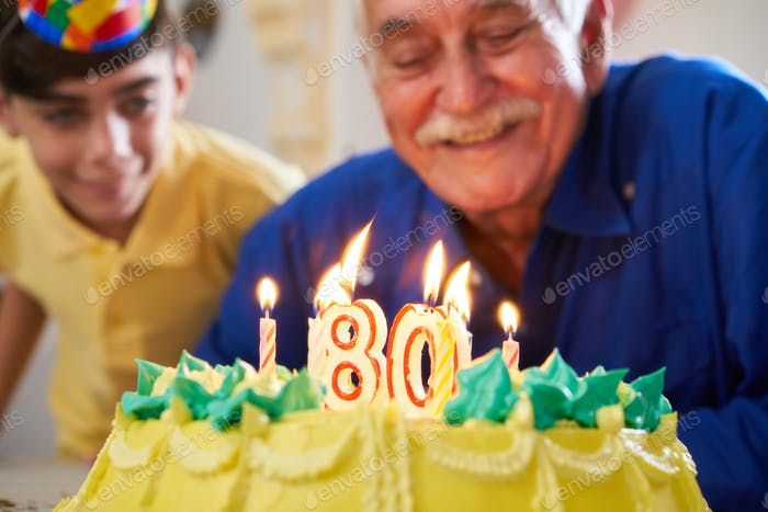 Boy and Senior Man Blowing Candles On Cake Birthday Party