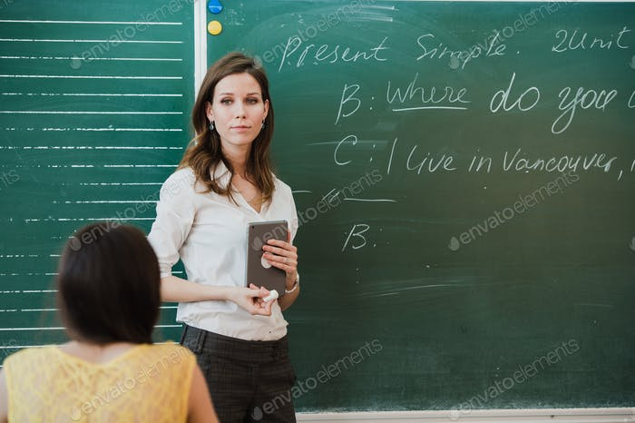 Young attractive female teacher of maths interacting with her young primary school students asking a