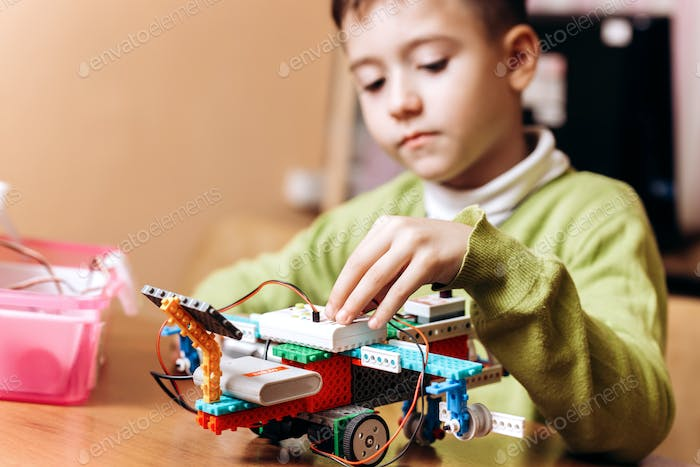 Boy dressed in green sweater sits at the desk with computer and looks at the robot that he made from