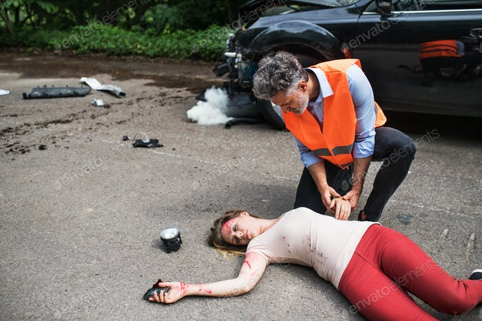 A man helping a young woman lying unconscious on the road after a car accident.