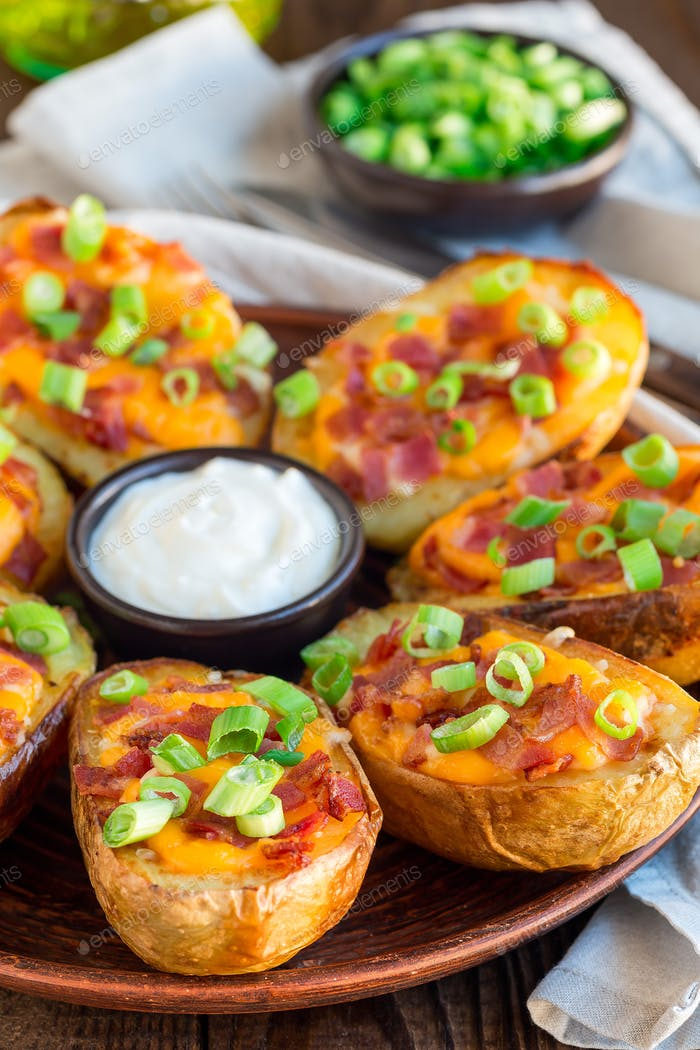 Baked loaded potato skins with cheddar cheese, bacon, garnished