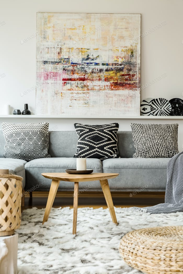 Painting above grey couch in boho living room interior with wood