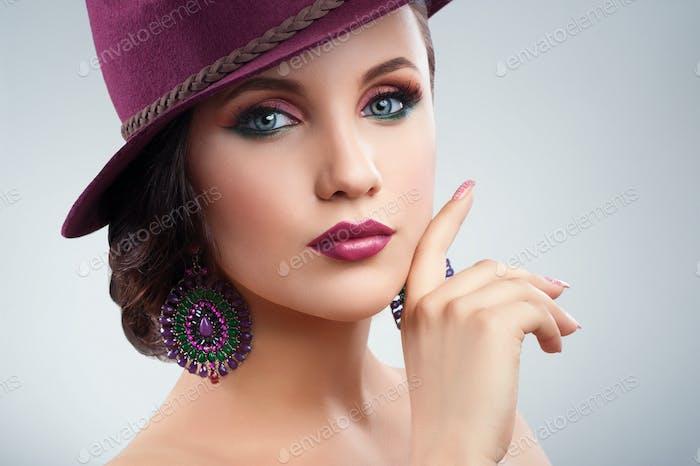 Wunderschöne elegante Frau in einem Hut posiert im Studio