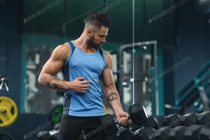 Handsome athlete training biceps with dumbbells at gym