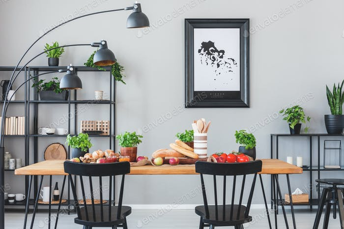 Lamp Above Black Chairs And Wooden Table With Food In Grey Dinin