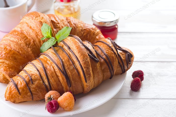 Fresh tasty croissants with berries on white wooden background