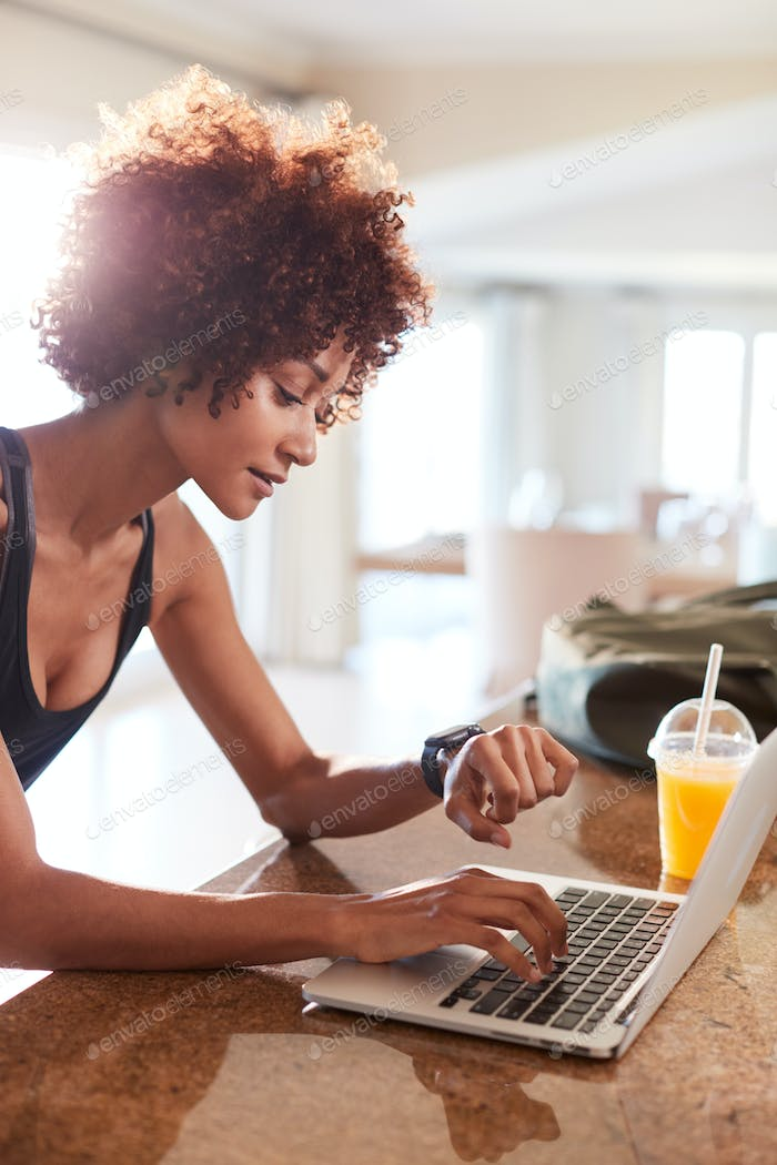 Millennial African American woman checking fitness app on watch and laptop after workout, vertical