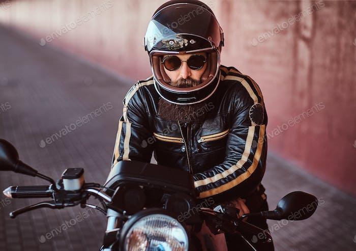 Brutal bärtiger Biker sitzt auf einem Retro-Motorrad mit einem mitgelieferten Scheinwerfer