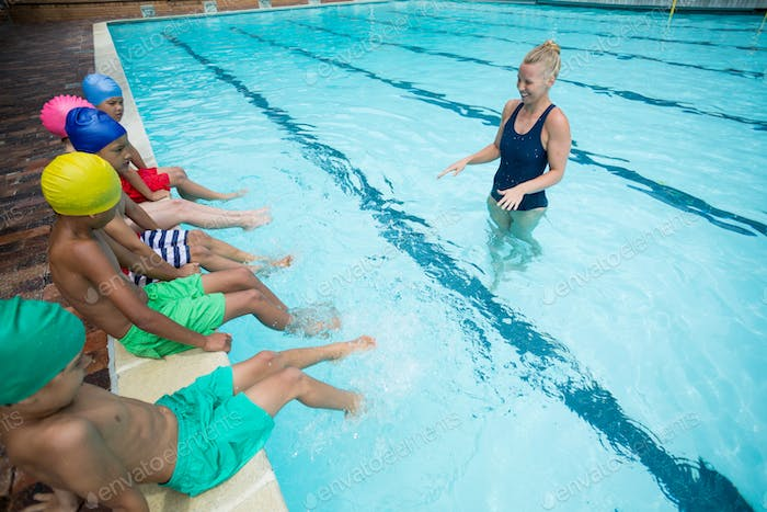 Confident female trainer instructing children in pool
