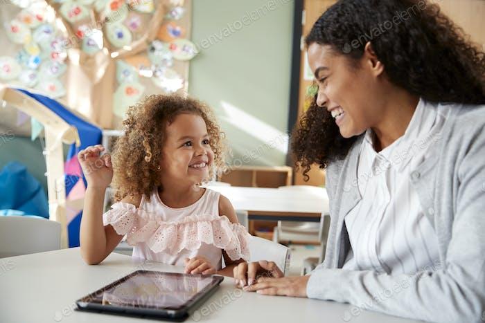 Weibliche Säuglingsschullehrerin, die eins zu eins in einem Klassenzimmer mit einem Tablet-Computer arbeitet