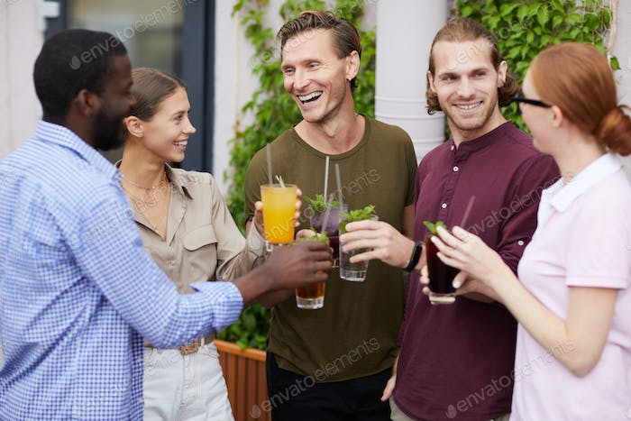 Group of Friends Enjoying Drinks at Party Outdoors