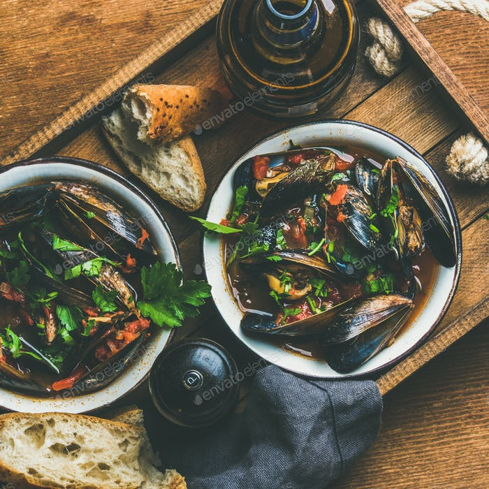 Belgian boiled mussels in tomato sauce with parsley in tray