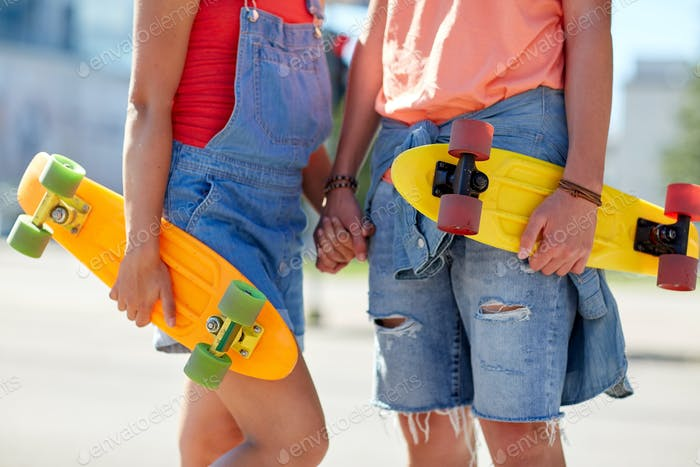 close up of young couple with skateboards in city