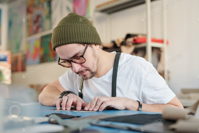 Professional leatherworker in beanie hat and t-shirt measuring piece of leather