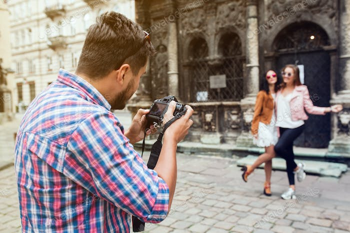 young handsome hipster man walking with photo camera