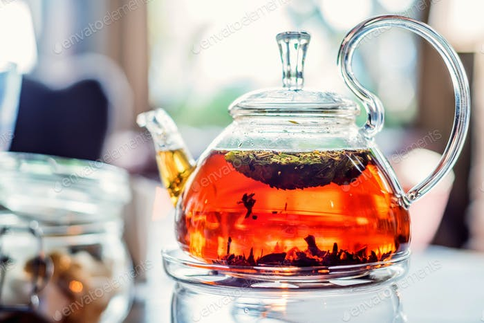 Modern glassy teapot with fresh tea