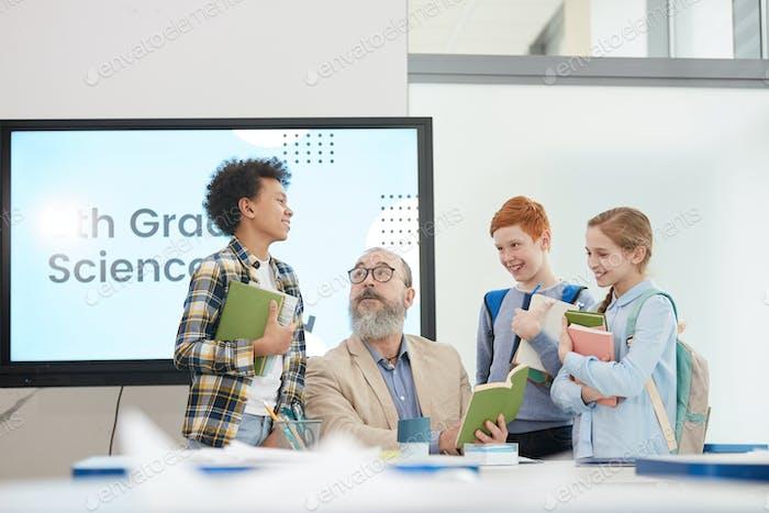Gruppe von Kindern im Gespräch mit Lehrer in der Schule