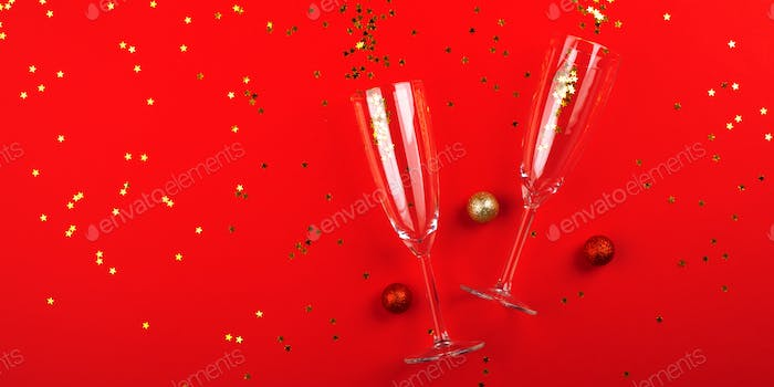 Champagne glasses with golden confetti on red