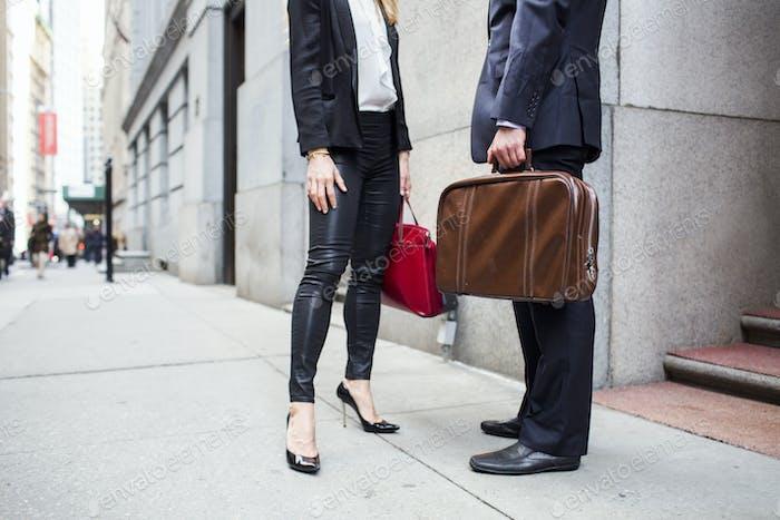 Niedriger Teil von Freunden in Businesswear stehend auf Bürgersteig durch Gebäude