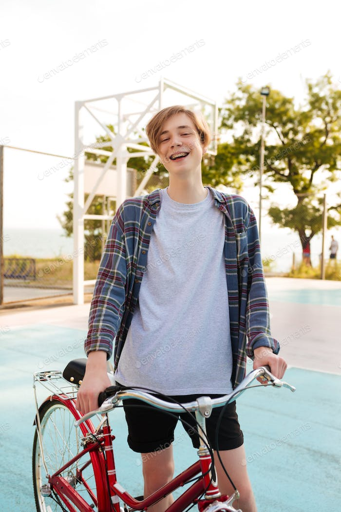 Portrait of smiling boy holding bicycle and happily looking in camera