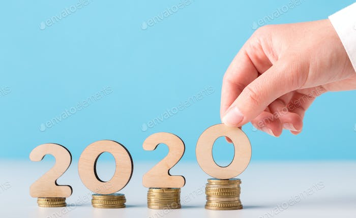 Man hand with 2020 concept on coins ascending