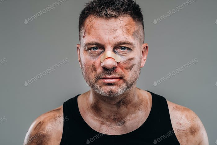 a battered man in a black T shirt who looks like a drug addict and a drunk stands against a gray