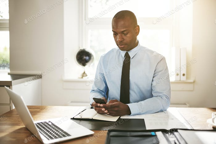 Young businessman reading text messages at his office desk