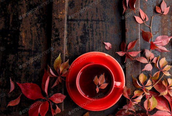 Autumn background with cup of tea and red leaves on dark background. Top view, copy space.