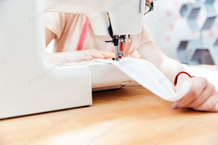 Seamstress sews clothes using white fabric