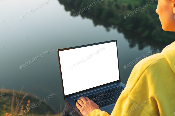 Young woman girl traveler freelancer in yellow hoodie with opened laptop, mock up