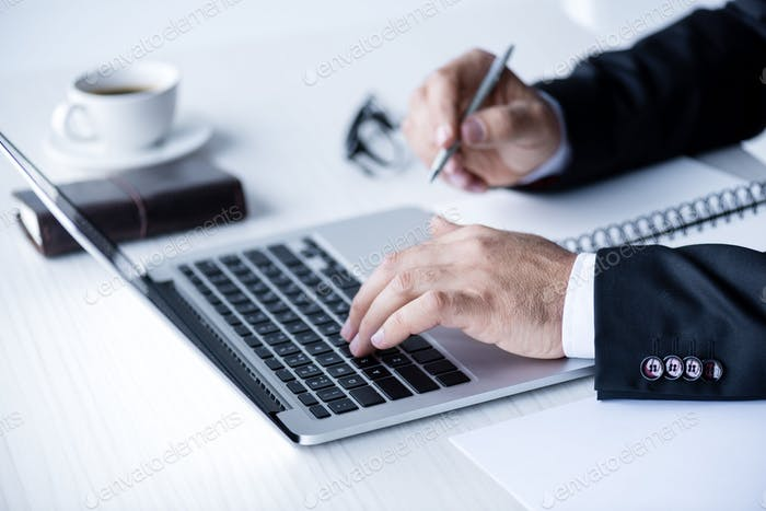 cropped view of businessman working with laptop and making notes