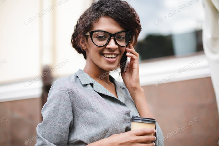 Cute African American girl in glasses standing on street and talking on her cellphone with coffee