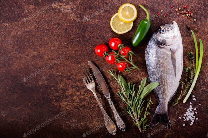 Fresh raw fish with lemon, herbs, onion, paprika, cherry tomatoes, onion, salt on rustic background