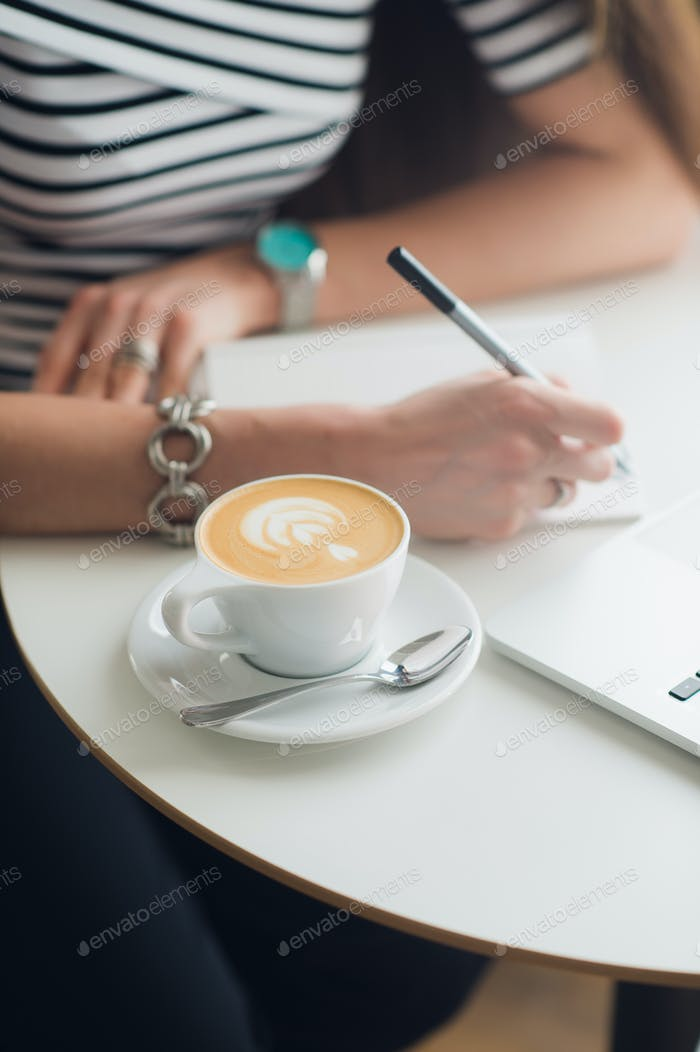 Close-up hands of woman holding a pen over empty notebook with cup of coffee next to it. Top view