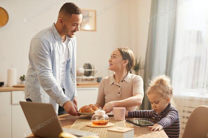 Moderne Familie mit Gadgets beim Frühstück in Cozy Kitchen