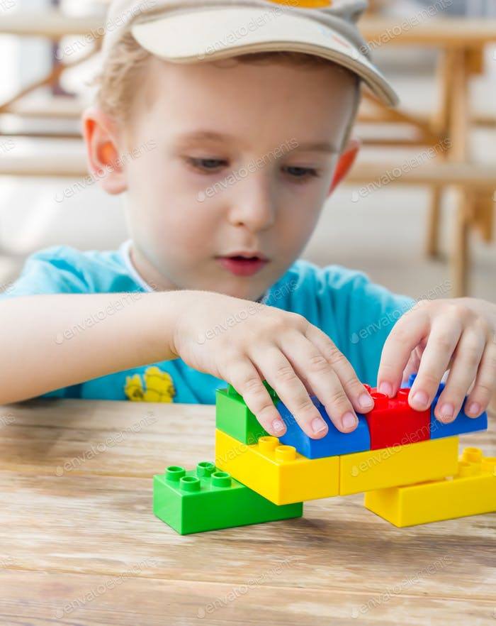 Little boy plays with plastic blocks
