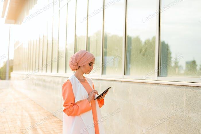 Porträt der arabischen Geschäftsfrau hält eine Tablette. Die Frau wird in einen abaya