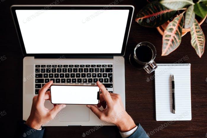diseño del ordenador portátil y el teléfono con lápiz de planificación portátil y empresario sosteniendo la pantalla blanca del teléfono
