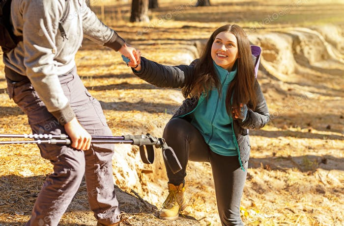 Smiling woman taking helping hand from man while hiking