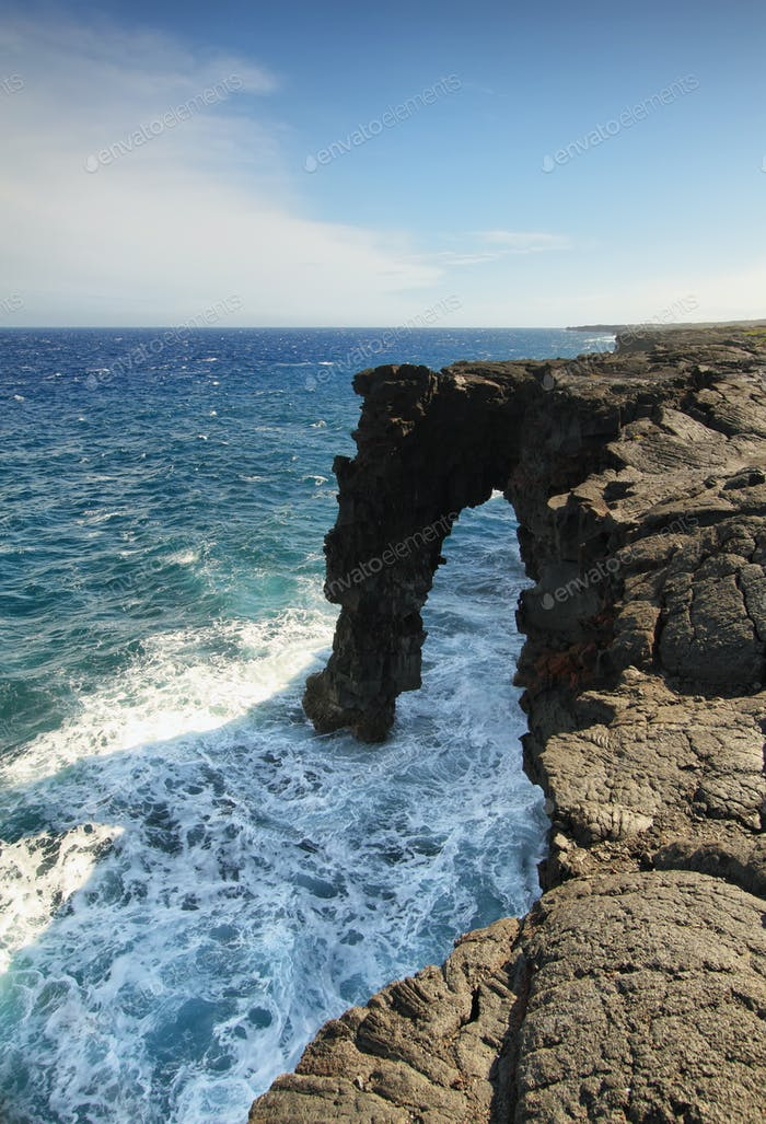 Natural arch in the black lava rock cliffs